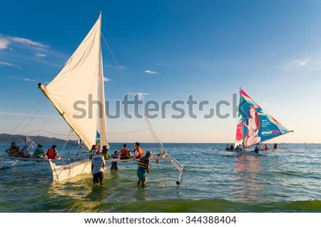 BORACAY, PHILIPPINES - MAY 17, 2015: Unknown tourists heading for a sunset sailing trip on a traditional philippine boat. - stock photo