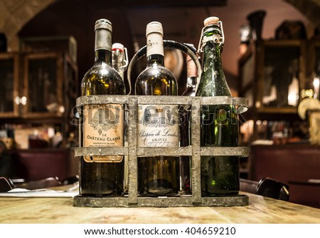 Bordeaux, France - March 24, 2016. Antiques french wine bottles from Bordeaux in a vintage metal bottle carrier. Aquitaine, France. - stock photo