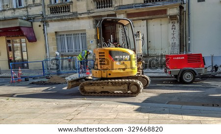 BORDEAUX, FRANCE, October 20, 2015 : Workers repairing water pipes in the street with their equipments, engines and a crawler dozer.