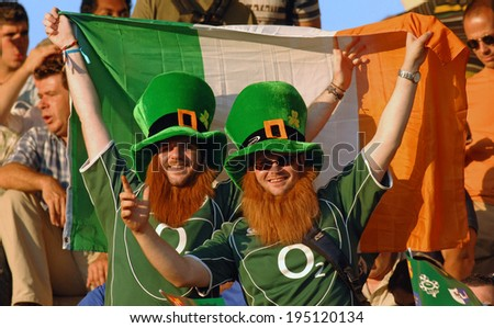 BORDEAUX, FRANCE-SEPTEMBER 09, 2007: irish fans cheering with the national flag during the match Ireland vs Namibia, of the Rugby World Cup, France 2007, in Bordeaux. - stock photo
