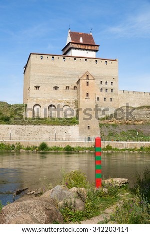Border between Russia and Estonia on the River Narva. Focus at the border post - stock photo