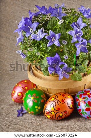 border card , blue flowers in basket with colorful easter egg on canvas sack texture background  - stock photo