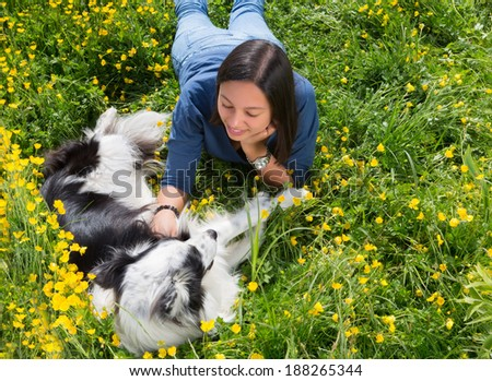 Border collie dog and young woman relaxing in the wildflowers of the park - stock photo