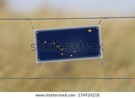 Border fence - Old plastic sign with a flag - Alaska - stock photo