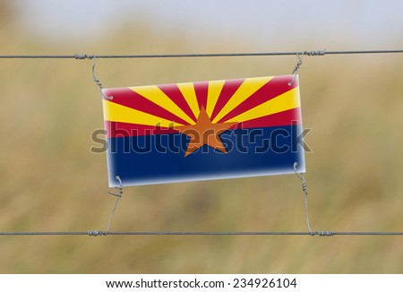 Border fence - Old plastic sign with a flag - Arizona - stock photo