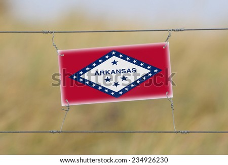 Border fence - Old plastic sign with a flag - Arkansas - stock photo
