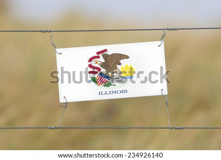 Border fence - Old plastic sign with a flag - Illinois - stock photo