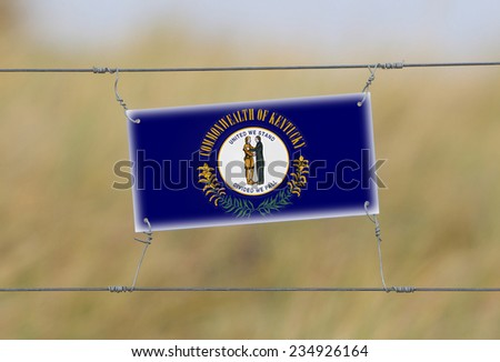 Border fence - Old plastic sign with a flag - Kentucky - stock photo