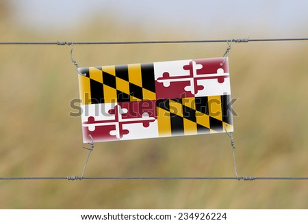 Border fence - Old plastic sign with a flag - Maryland - stock photo