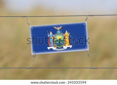 Border fence - Old plastic sign with a flag - New York - stock photo
