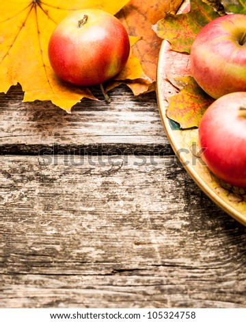 Border from apples and autumn leaves on old wooden table. Thanksgiving day concept - stock photo
