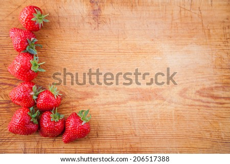 Border from fresh strawberries with copy space and a wooden background