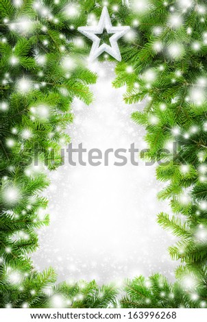Border made of fir twigs and snow building the empty shape of a Christmas tree - stock photo