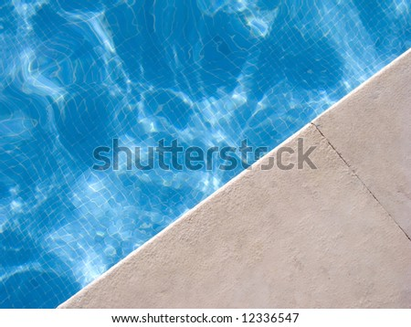 border of a swimming pool with blue water - stock photo