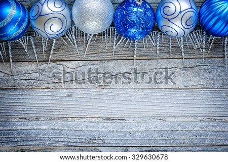 Border of Christmas blue and silver balls on top of an old wooden board, copy space for text, top view.