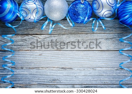 Border of Christmas blue and silver balls on top of an old wooden board, top view. Copy space for text.