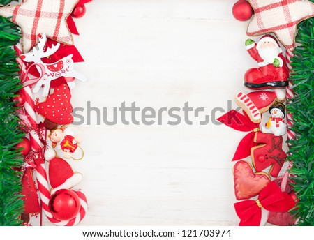 Border of christmas decoration and cookies on white wooden background - stock photo