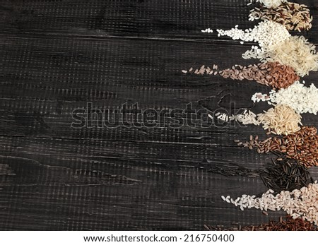 Border of colorful varieties whole grain rice in a rustic wooden surface background - stock photo