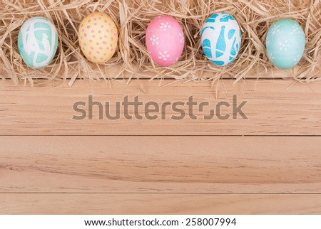 Border of Easter eggs and raffia on wood background - stock photo