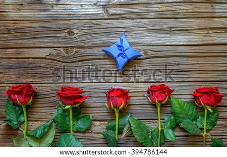 Border of five fresh red roses and a decorative blue Valentines gift arranged on a rustic wooden background with copy space - stock photo