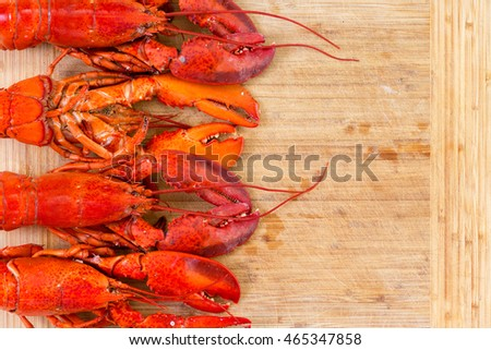 Border of four red lobsters neatly arranged at the side on a wooden cutting board with one upside down to show the underside with copy space, overhead view