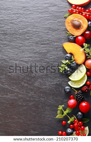 Border of fresh fruit and herbs along the right of the frame with assorted berries, apricot, peach and lemon on a dark grey slate background with copyspace - stock photo