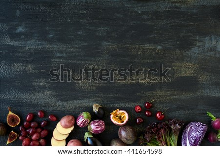 Border of fresh purple toned vegetables and fruits on dark rustic distressed background, eggplant, carrot, fig, aubergine, grapes, radishes, leaf lettuce, passionfruit, cherries