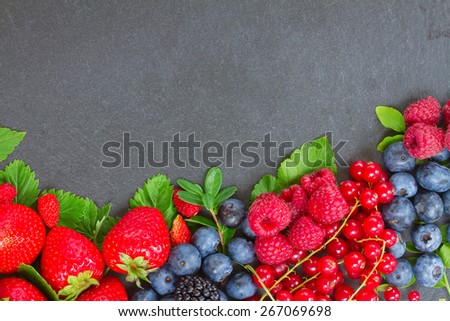 border  of fresh ripe  berries with green  leaves with copy space  on black stone background - stock photo