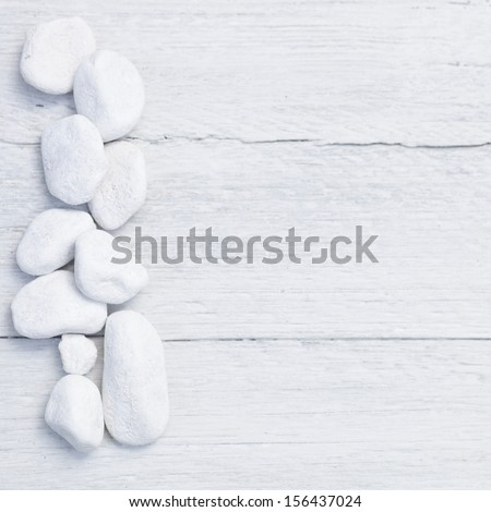 Border of natural white pebbles on the side over a textured painted white background of rough wooden boards with copyspace for your greeting or text, conceptual of spa treatments