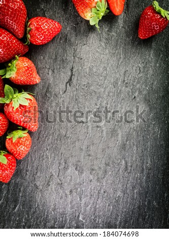 Border of whole fresh ripe red strawberries arranged on two sides on a dark grey textured slate background with copyspace and vignetting - stock photo