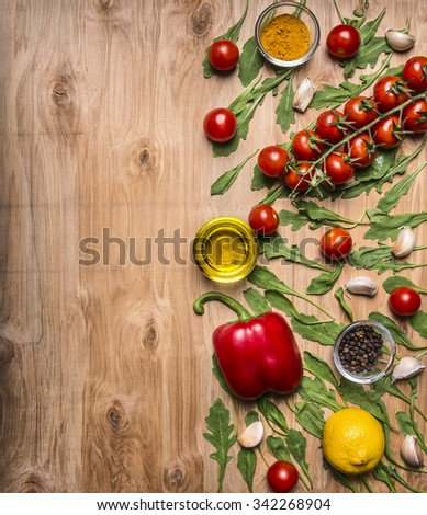 border with oil, cherry tomatoes on a branch, pepper, seasoning, arugula, garlic border ,with text area on wooden rustic background top view - stock photo