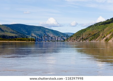 Boreal forest hills at river bank of Yukon River, Yukon Territory, Canada, near Dawson City forming a beautiful northern riverscape. - stock photo