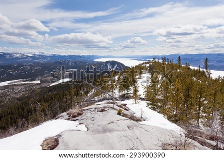 Boreal forest taiga wilderness with still frozen ice surface of Lake Laberge end of April at spring time in the Yukon Territory, Canada - stock photo