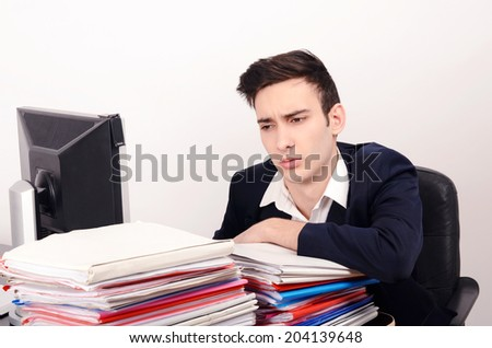 Bored and worried business man with a lot of work. Unhappy worker with a big pile of files to work on. - stock photo