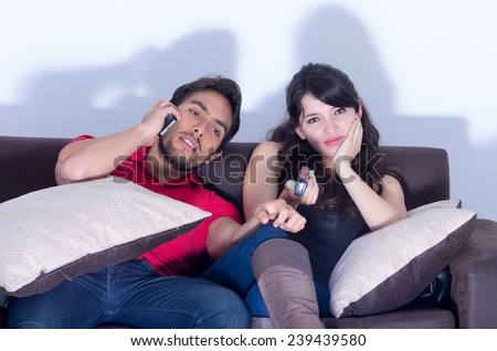 bored annoyed girlfriend watching television while boyfriend chats on the phone - stock photo