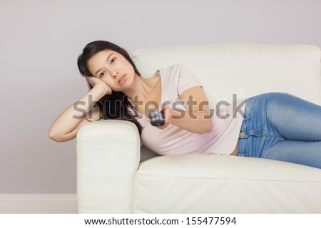 Bored asian girl lying on the couch watching tv at home in the sitting room - stock photo