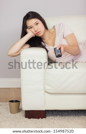 Bored asian girl lying on the sofa watching tv at home in the sitting room - stock photo