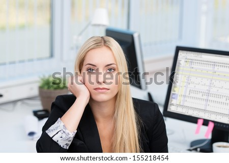 Bored attractive young businesswoman sitting at her desk in the office staring straight at the camera with a serious expression
