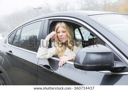 Bored attractive young woman sitting waiting in a car staring out through the open window with a glum expression