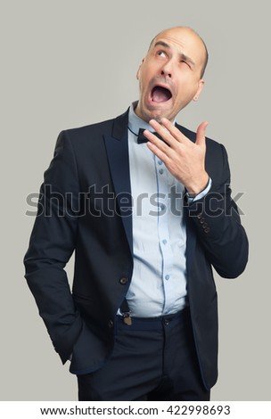 bored bald stylish man yawning and looking up. Gray background