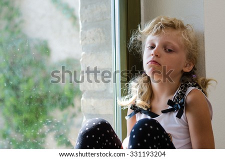 bored blond girl sitting alone by the window