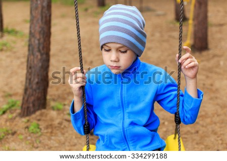 Bored boy in the park. Bored boy at the park sitting on the swing his eyes downcast - stock photo