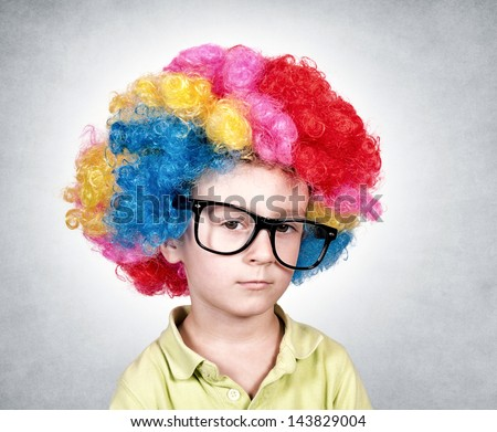 Bored boy with the clown wig on head - stock photo