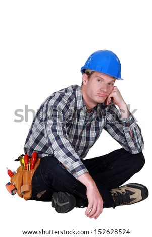 Bored builder sat on the floor - stock photo