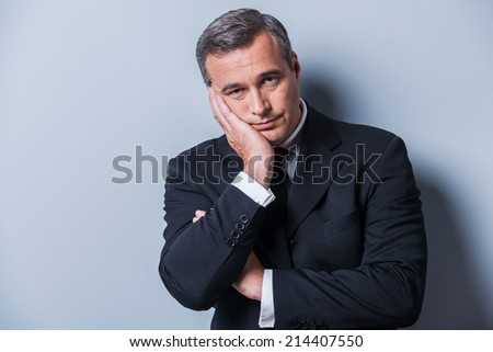 Bored businessman. Bored mature man in formalwear holding head in hand and looking at camera while standing against grey background - stock photo