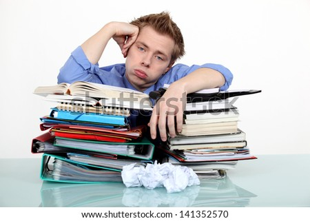 Bored businessman leaning on a stack of files - stock photo