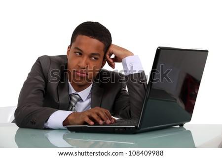 Bored businessman sat at his desk - stock photo