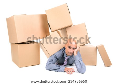 Bored businessman under a pile of cardboard boxes - stock photo