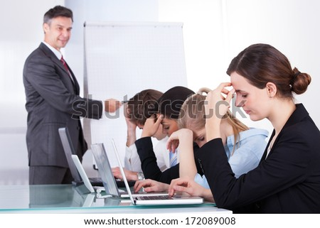 Bored Businesspeople At Presentation With Colleagues In Office - stock photo