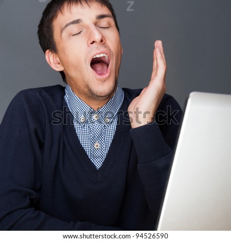 Bored businesspeople: man sitting at desk yawns. Young multiethnic latin caucasian business man at his office. - stock photo